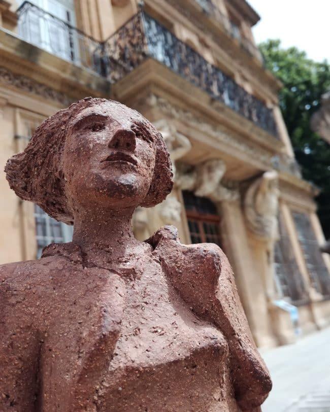 Modelage de femme en grès, devant le Pavillon Vendôme
